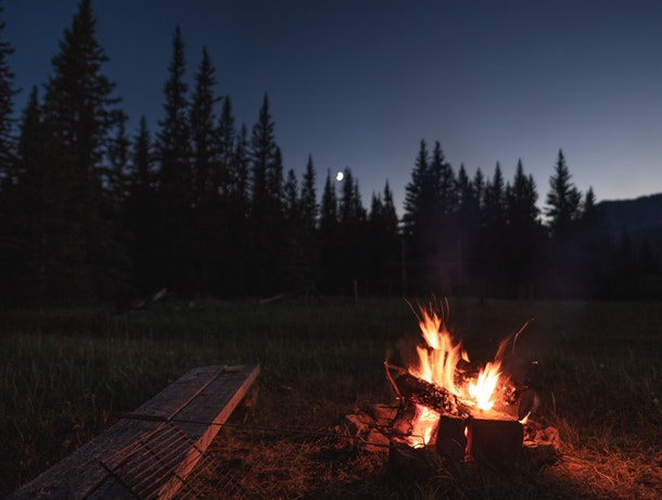 Campfire under the out of focus moon. There is a wooden bench beside the campfire with a hot dog / marshmallow roasting stick laying on the bench. There is a silhouette of the trees in the background.