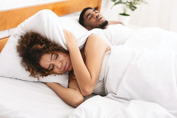 Snoring man is annoying. Young african-american woman suffering from her noisy sleeping boyfriend