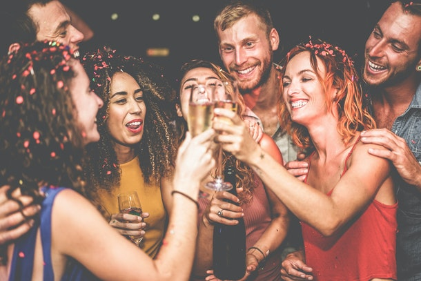 Group of happy friends cheering with champagne at new year's eve party - Young people having fun at trendy holiday fest - Youth trends and celebrating concept - Focus on right girl face