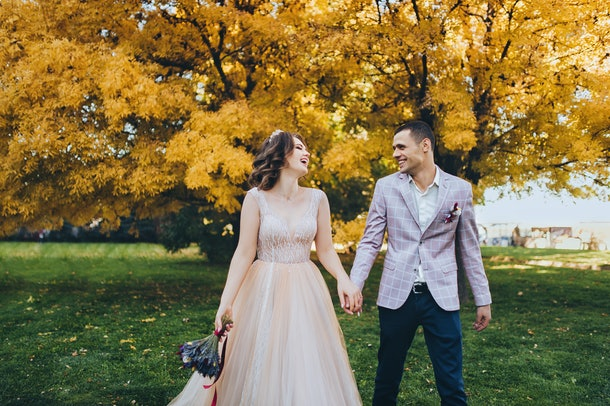Newlyweds in love walk in the fall in the park with yellow foliage. Stylish groom in a plaid jacket leads the hand of a cute bride in a beige dress with a crown. Wedding photography. Princess Bride.