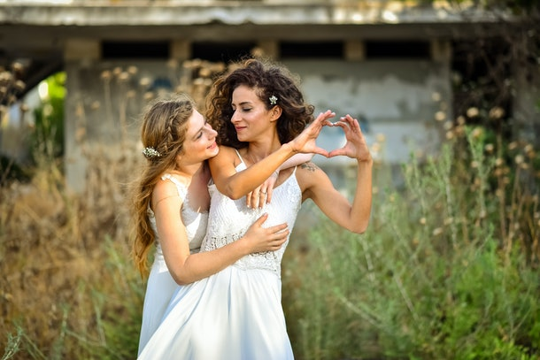 two brides white dresses, one creates a heart shape using the fingers of the hands. the other one looking her. farm at the background.