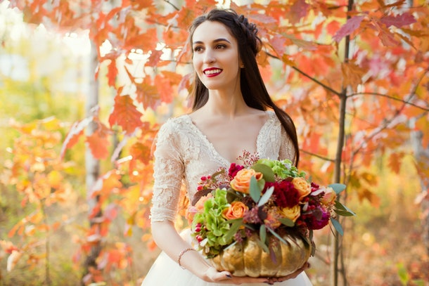 beautiful bride with flowers in the golden pumpkin