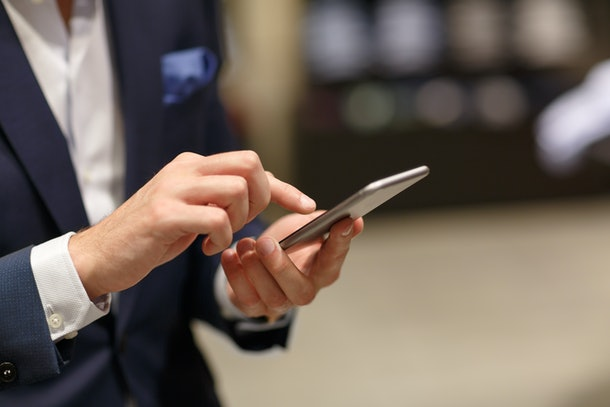 Close-up of hands of unidentified successful man in formal suit typing text in smart phone against background of  blurry interior of fashion boutique