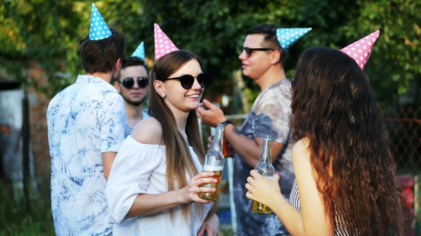 Two happy woman talking and drinking beer from bottle on summer party, men in the background, wearing holiday caps