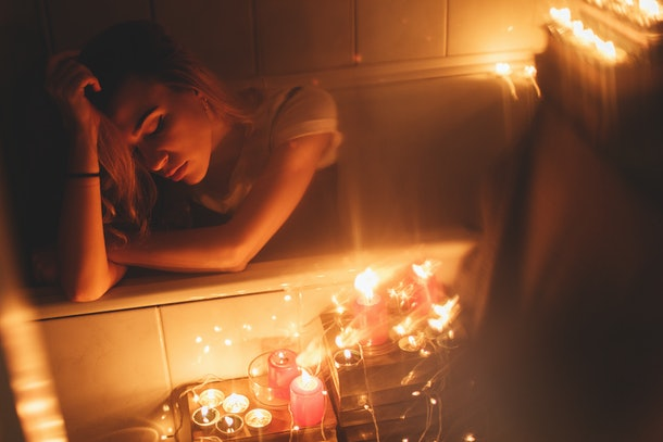 Red candles burning, Christmas lights and garland in bathroom on back bath. Romantic , Valentine's day. Attractive woman relax in bath.