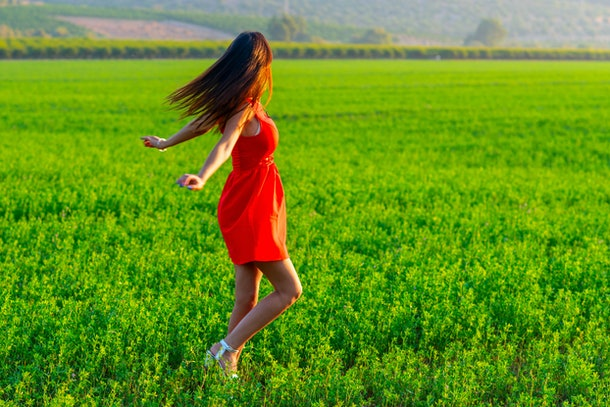 Young woman happily twirling in her summer red dress. Girl Spinning in a green field at sunny day. Happy, health, travel, lifestyle concept.