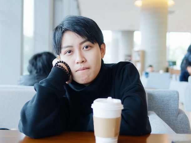 Portrait of cute beautiful young lesbian with short haircut and trendy boyish clothes sitting in coffee shop, friendly Chinese gay girl.