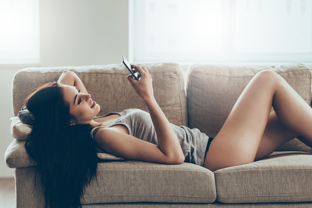 Typing message to him. Beautiful young woman in panties and tank top holding smart phone and looking at it with smile while lying on couch at home