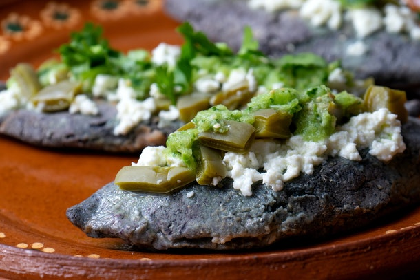Traditional mexican tlacoyos with green sauce and nopal cactus