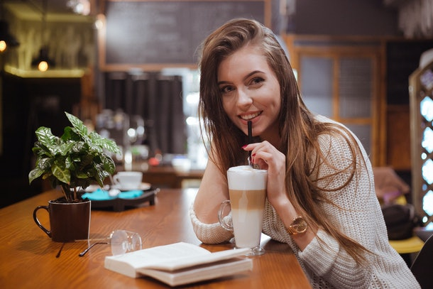 Preaty girl with big latte and book in coffee house