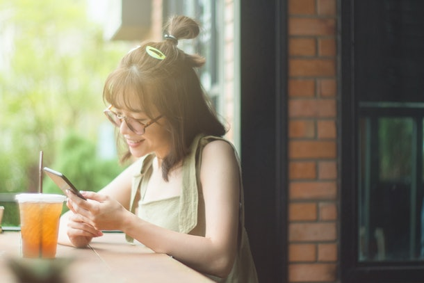 Portrait of cute asian teen woman using smartphone at coffee cafe. texting with someone. reading pleasant text message on mobile phone while happy smile chill out. technology communication concept