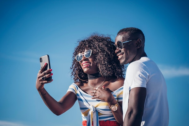Couple of Africans taking a selfie with a mobile phone.