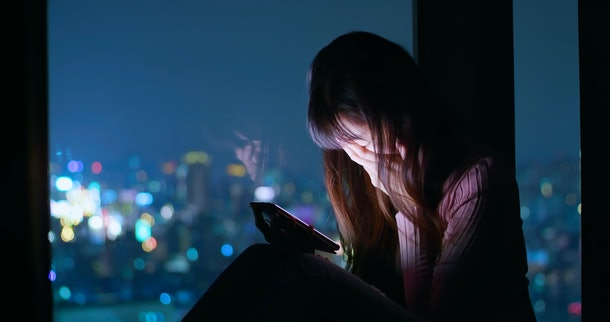 woman use phone and feel depression at night