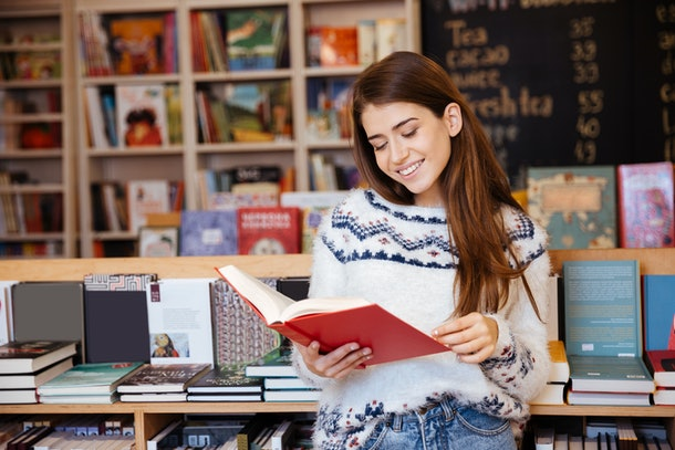 Portrait of a pretty smiling girl reading book indoors in library