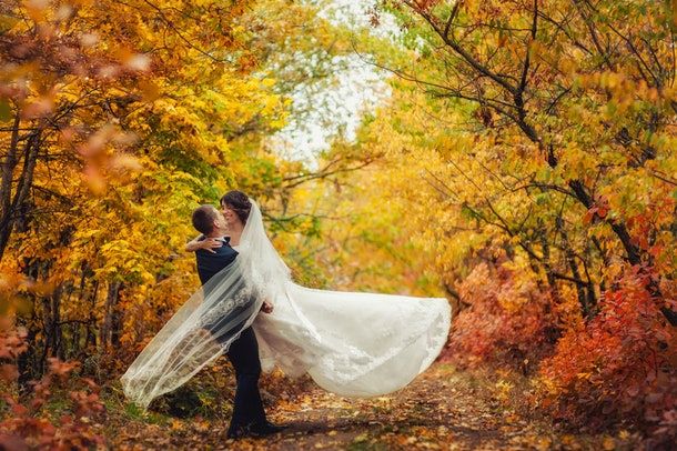 Happy young newly married wedding couple on walk in golden yellow fall autumn park around trees. Groom circling bride in beautiful white dress. Relationship love concept. Man woman on nature outdoors