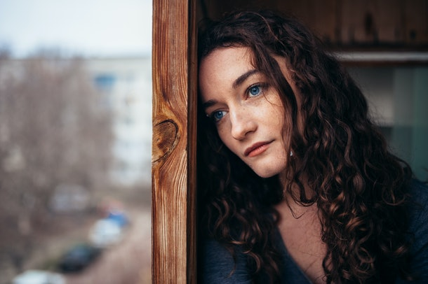 beautiful sad lonely girl sitting near the window is missing