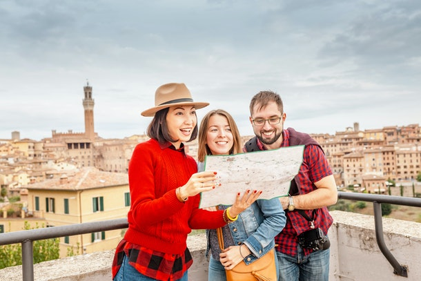 Multiracial group of friends tourists looking at map in an old city in Italy. Travel and adventure concept
