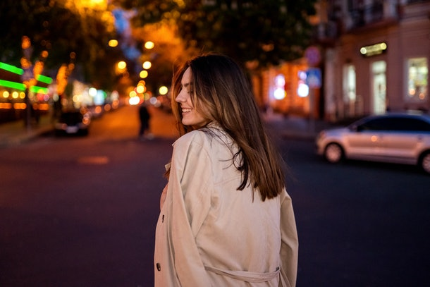 Beautiful brunette girl walks through the night city. Standing back. Awesome bokeh.
