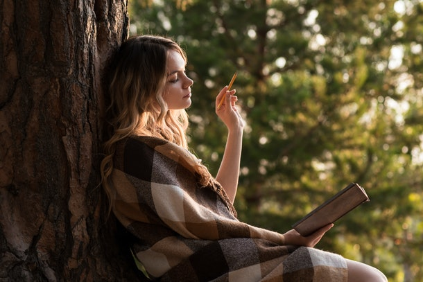 A girl sits leaning on a tree writing in a notebook outdoors.  Checkered plaid on shoulders. Thoughtful look in notebook. Raised hand with a pencil. Sunset. In the forest.