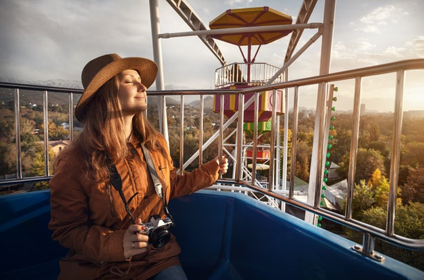 Woman with hat and vintage camera at the cabin of Ferris wheel in the autumn park at sunset