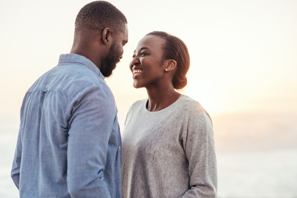Smiling young African woman talking and laughing with her boyfriend while standing together on a beach at sunset