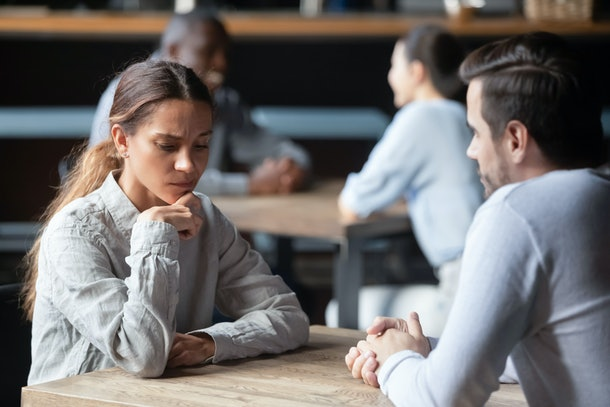 Shy or bored mixed race woman sitting at table in cafe during speed dating indifferent to the conversation lost in thoughts, unsuccessful first acquaintance unlucky failure of romantic date concept