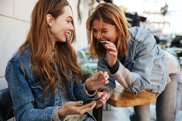 Two young pretty girls in casual stylish wear laughing while sitting at cafe