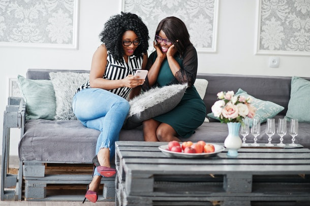 Two african woman friends wear on eyeglasses sitting at couch indoor white room and looking with surprised faces at mobile phone.