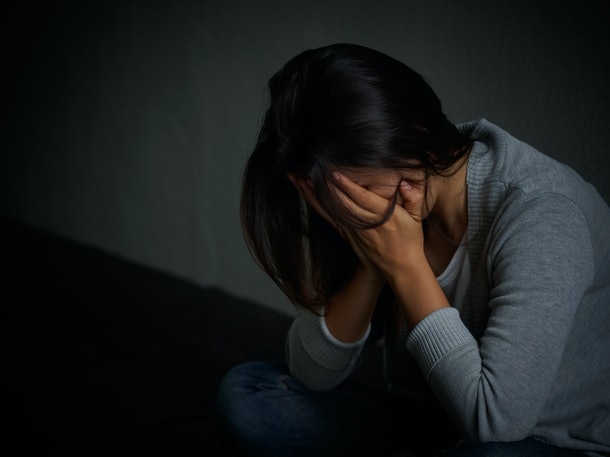 sad woman hug her knee and cry. Sad woman sitting alone in a empty room.