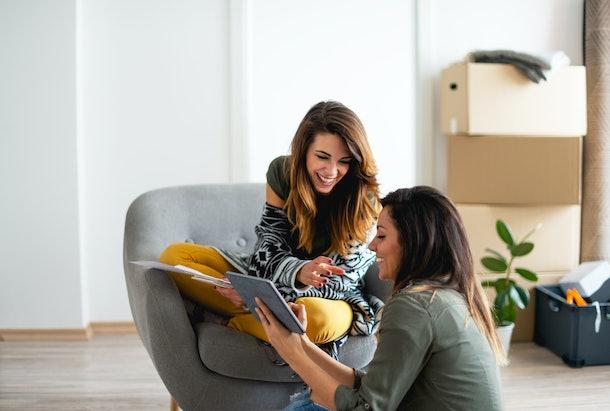 Happy lesbian couple renovating apartment
