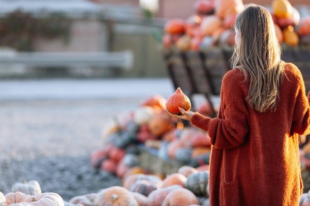 Back view of woman with small pumpkin in hand near wooden wagon with pumpkin on farmers market in brown sweater. Cozy autumn vibes Halloween, Thanksgiving day.