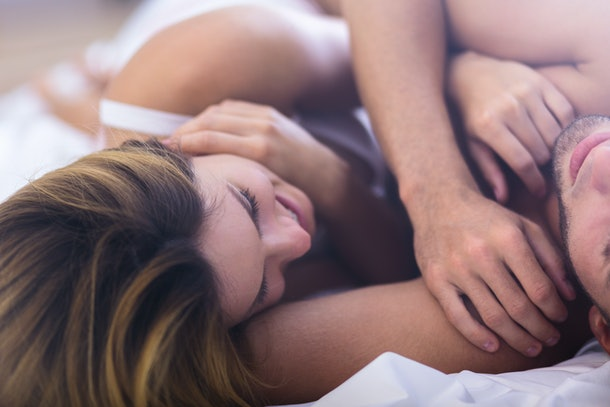 Close-up of happy young woman in bed with boyfriend