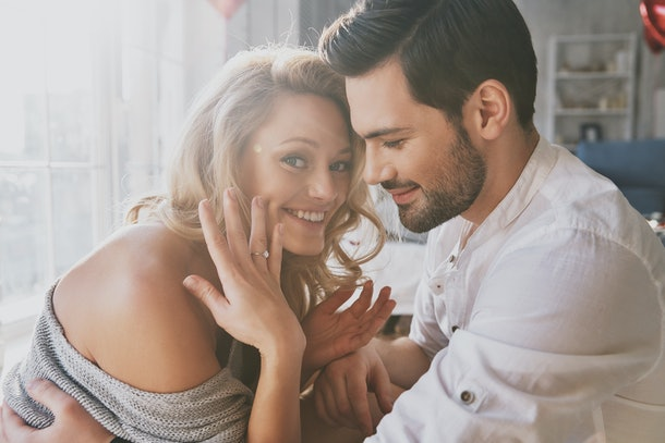 So happy! Beautiful young woman showing her engagement ring and smiling while sitting in the bedroom with her boyfriend