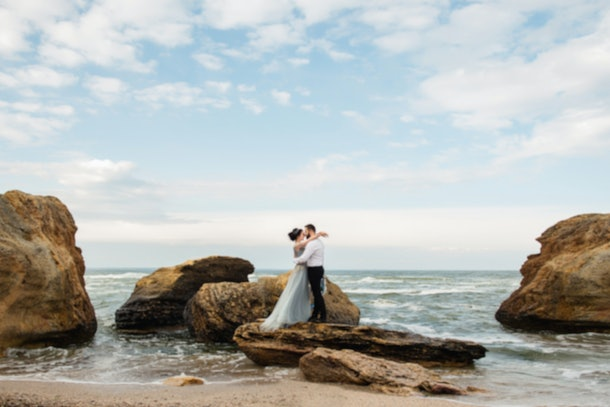 Blurred image of wedding couple by the sea. Wedding sea background