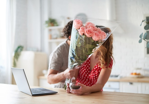 Summer holidays, love, relationship - couple with bouquet of flowers in the kitchen. Laptop on the table.
