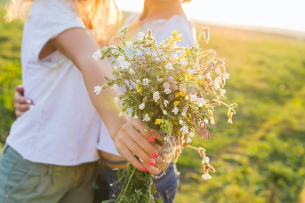 people, homosexuality, same-sex marriage and love concept - close up of happy lesbian couple with flower bunch on nature