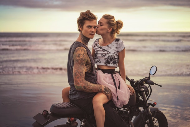 girlfriend kissing boyfriend on motorcycle on ocean beach during beautiful sunrise