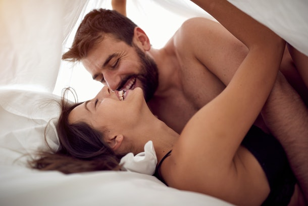Young happy lovers man and woman making love in bed- Passionate sex