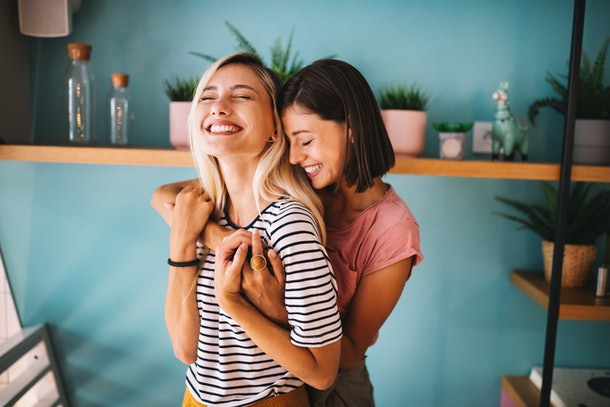 A lesbian couple embraces and smiles while spending the day together.