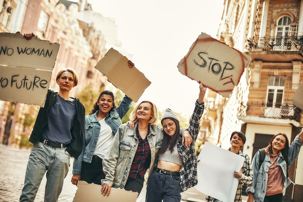Girl power. Group of young and happy female activists standing on the road during protest march and holding signboards with different slogans