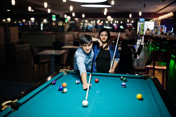A couple plays pool at a local bar while on a hometown date.