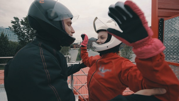 Male coach instructs a skydiver girl before flying into wind tunnel
