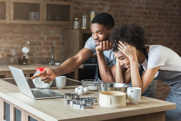 Shocked african-american couple baking with recipe on laptop in loft kitchen