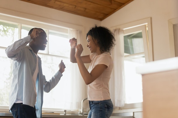 Excited african American millennial husband and wife have fun celebrating anniversary at home, smiling happy biracial young couple dancing in kitchen feel overjoyed moving in new house together