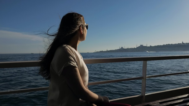 happy woman in sunglasses with waving hair travels by ship and enjoys magnificent seascape under sunshine closeup