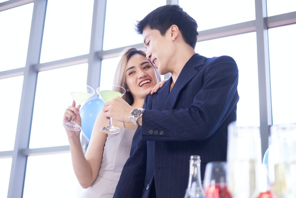 Asian romantic couple holding wine glasses celebrating romance Valentine's day. The married couple have private happy Valentine's day celebration by drinking wine. Relationship & Birthday concept.