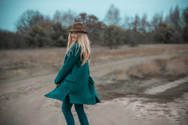 Woman of plus size, American or European appearance walks at the nature. A young lady with excess weight, stylishly dressed in warm clothes, Natural beauty