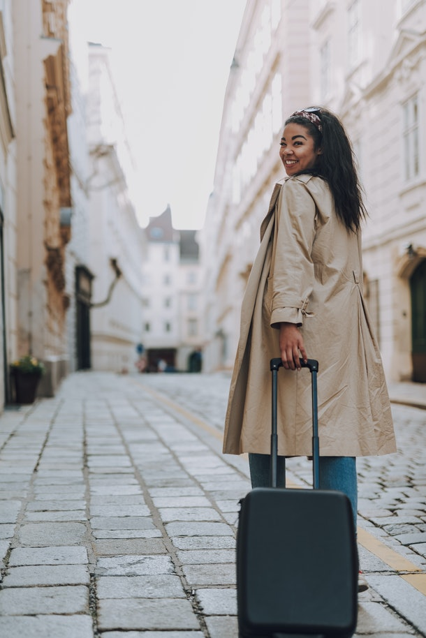 A happy woman rolls her suitcase down a city street in Europe while on vacation.
