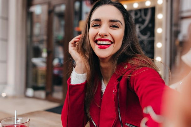 A happy brunette woman in a red outfit takes a selfie while sitting outside a café on Valentine's Day.