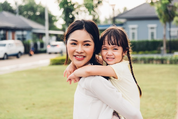 A young woman and her niece hang out in a park on a sunny day.
